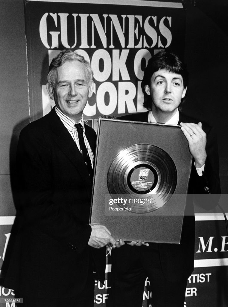 England, 24th October 1979, Former Beatle Paul McCartney with 'Guinness Book of Records' chief Norris McWhirter hold up a unique Rhodium disc which was presented to the musician for achieving the title of 'Most Successful composer of all time' : Nachrichtenfoto