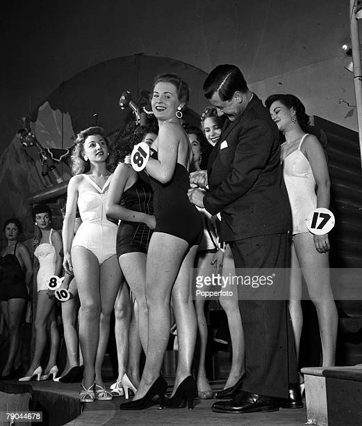 England A picture at a heat in the Miss Britain beauty contest showing competition organiser Eric Morley freeing a jammed zipper on a contestants...