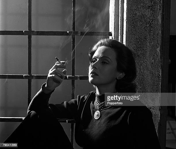 England A portrait of actress Nadia Gray smoking a cigarette at home