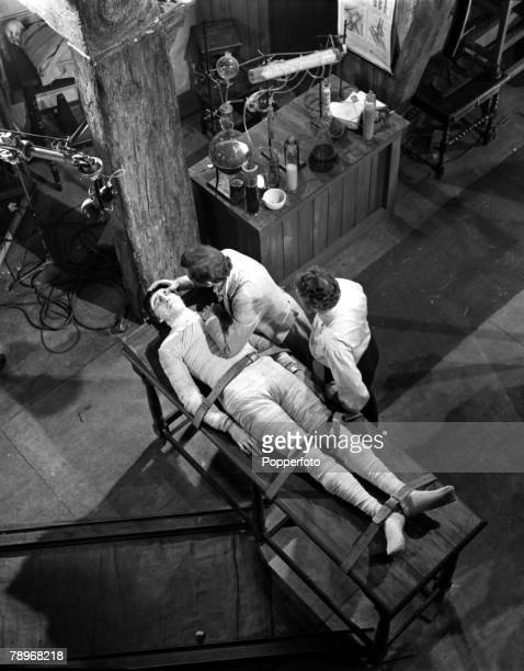 England A scene from the film 'The Curse of Frankenstein' showing actors Christopher Lee on the table with Peter Cushing and Robert Urquart standing...