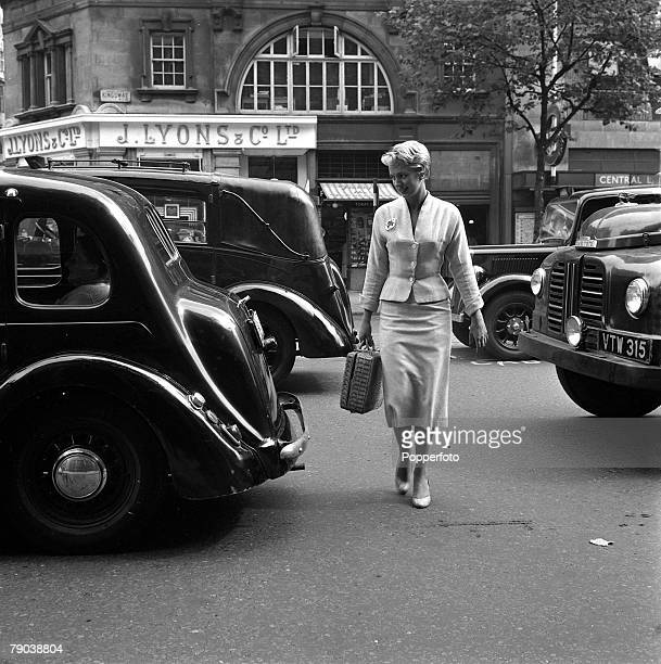 England A smartly dressed young lady wearing nylon stockings crosses the road avoiding the traffic