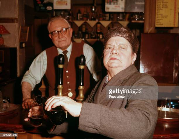 England Actress Violet Carson who plays the role of Ena Sharples in the ITV soap opera Coronation Street is pictured pouring a drink at the bar of...