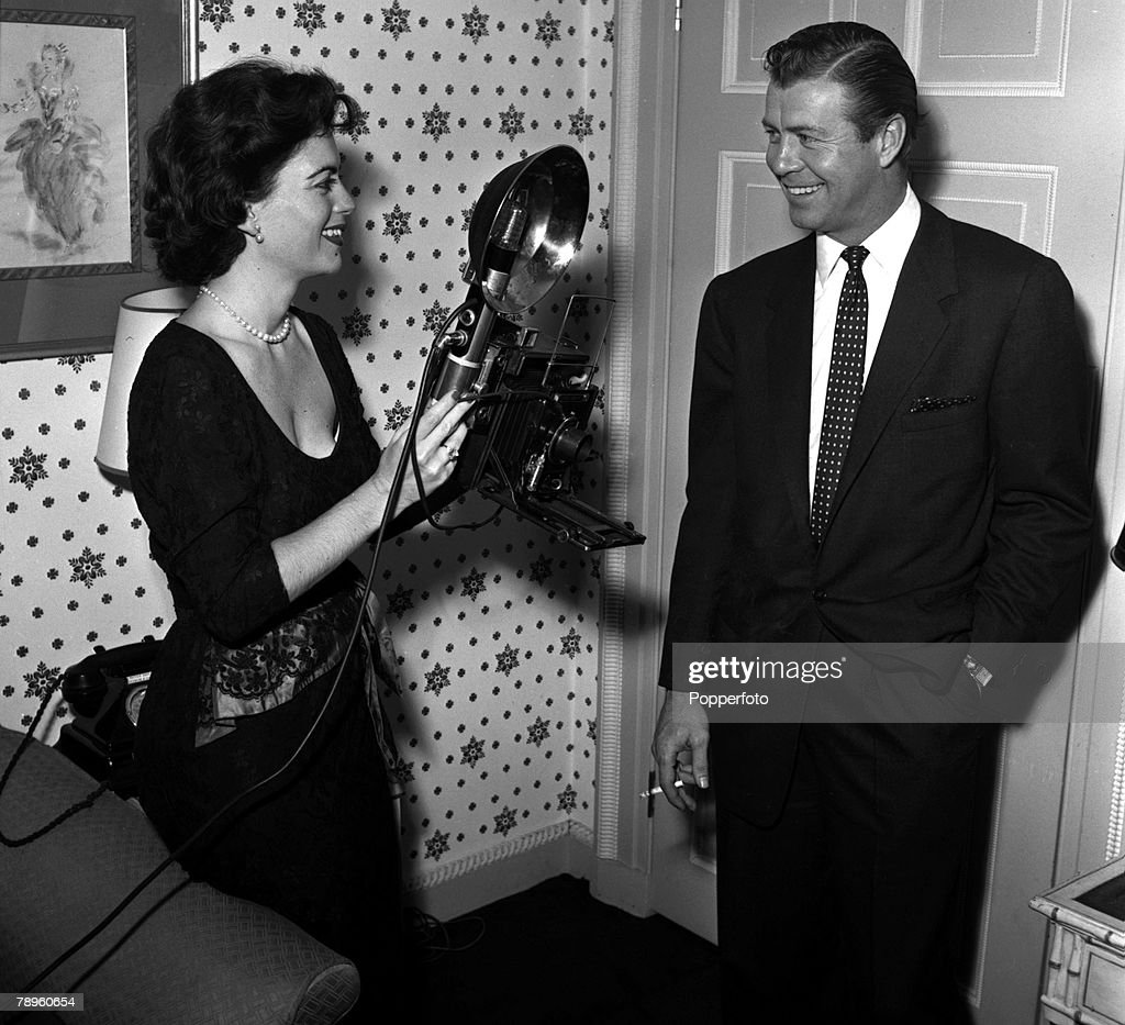 England. 1955. American actress Faith Domergue is pictured taking a photograph of actor Gene Nelson at a press reception. : News Photo