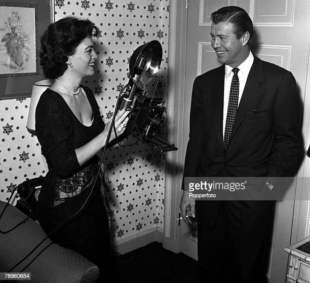 England American actress Faith Domergue is pictured taking a photograph of actor Gene Nelson at a press reception