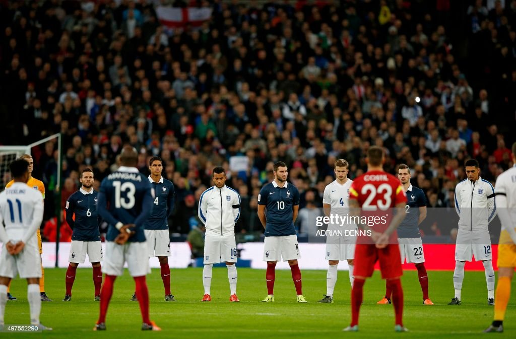 England and France squad members observe a minute's silence before the start of the friendly football match between England and France at Wembley Stadium in west London on November 17, 2015.