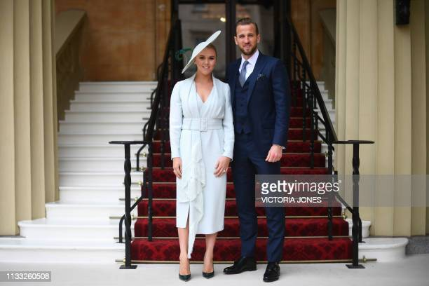 England and Totthenham Hotspur football player Harry Kane poses with his partner Kate Goodland as they arrive at Buckingham Palace before attending...