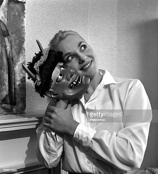 England Australian actress Diane Cilento is pictured holding a mask