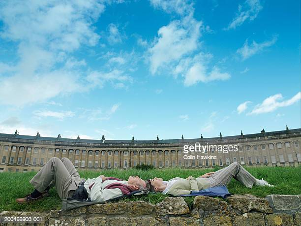 england, bath, mature couple relaxing on grass by the royal crescent - colin hawkins stock pictures, royalty-free photos & images