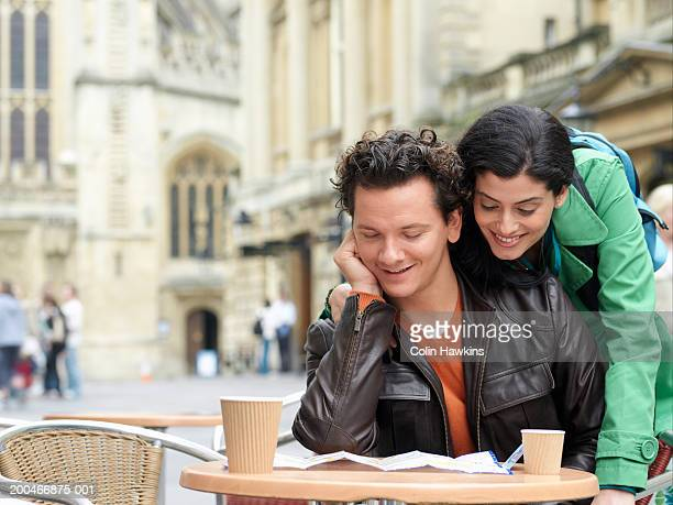 England, Bath, young couple at cafe table, looking at map, outdoors