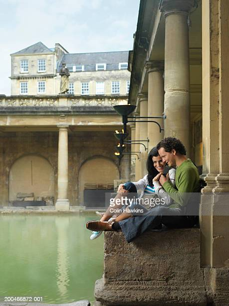 England, Bath, young couple relaxing at side of Roman Spa