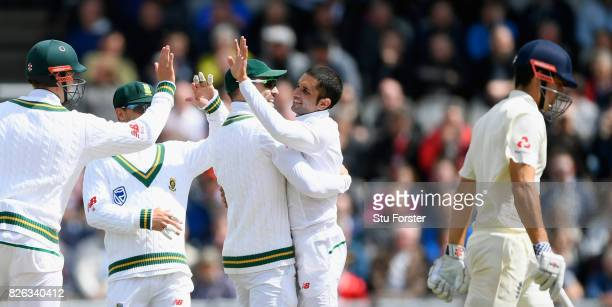 England batsman Alastair Cook leaves the field after being caught behind by Quinton de Kock as bowler Keshav Maharaj celebrates with team mates...