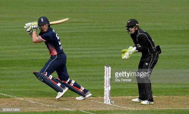 England batsman Ben Stokes hits out watched by Tom Latham during the 3rd ODI between New Zealand and England at Westpac stadium on March 3 2018 in...