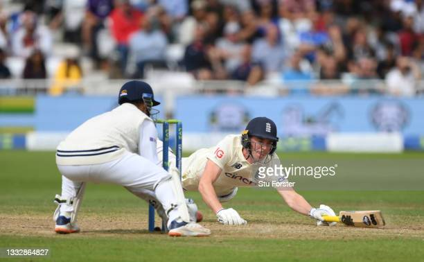 England batsman Dan Lawrence dives to make his ground as Rishbah Pant looks on during day four of the First Test Match between England nd India at...