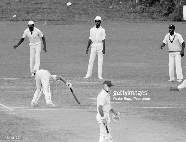 England batsman David Gower manages to avoid falling onto his own wicket after trying to avoid a bouncer from West Indies bowler Michael Holding as...