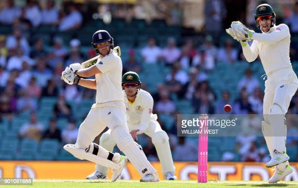 England batsman Dawid Malan cuts a ball away in front of Australia's wicketkeeper Tim Paine and fieldsman Cameron Bancroft on the first day of the...
