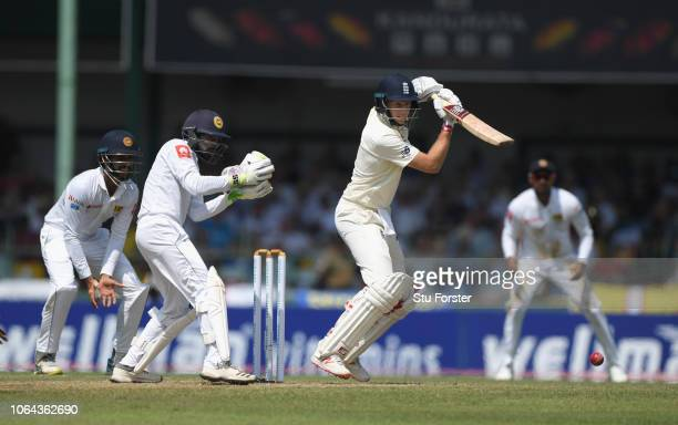 England batsman Joe Root cuts a ball towards the boundary watched by wicketkeeper Dickwella during Day One of the Third Test match between Sri Lanka...