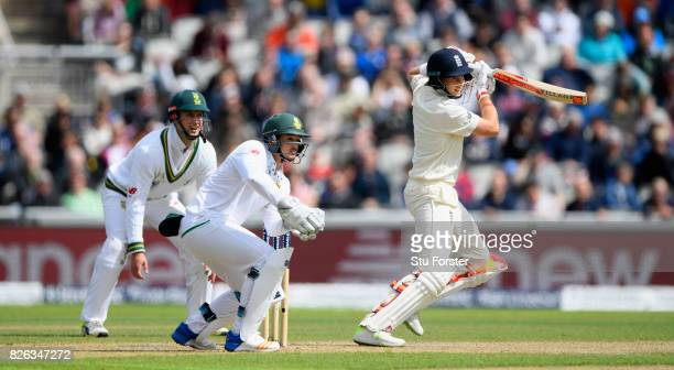 England batsman Joe Root cuts a ball towards the boundary watched by Quinton de Kock who is congratulated by team mates during day one of the 4th...
