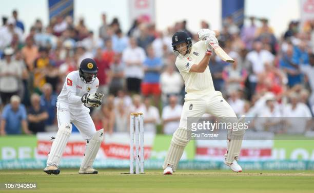 England batsman Joe Root cuts the ball for runs watched by Niroshan Dickwella during Day One of the First Test match between Sri Lanka and England at...