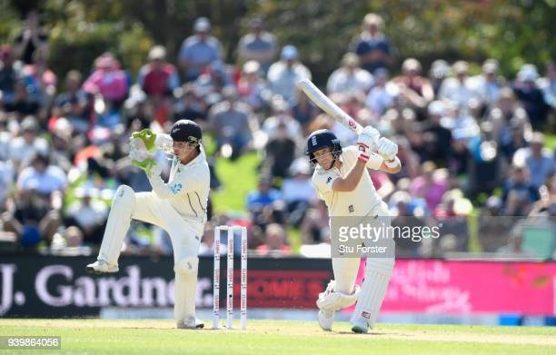 England batsman Joe Root hits out watched by BJ Watling during day one of the Second Test Match between the New Zealand Black Caps and England at...