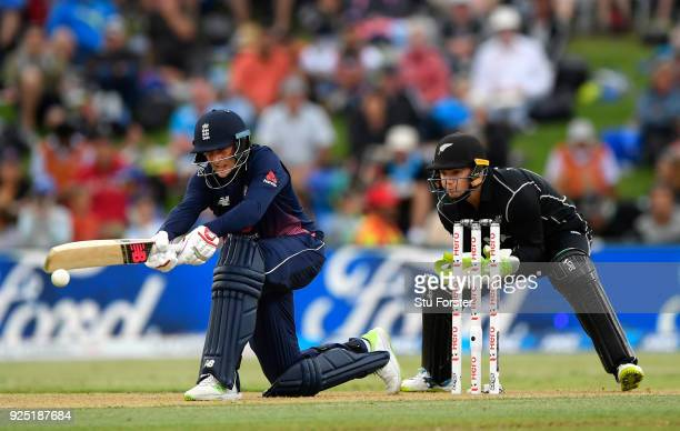 England batsman Joe Root hits out watched by Tom Latham during the 2nd ODI between New Zealand and England at Bay Oval on February 28 2018 in...