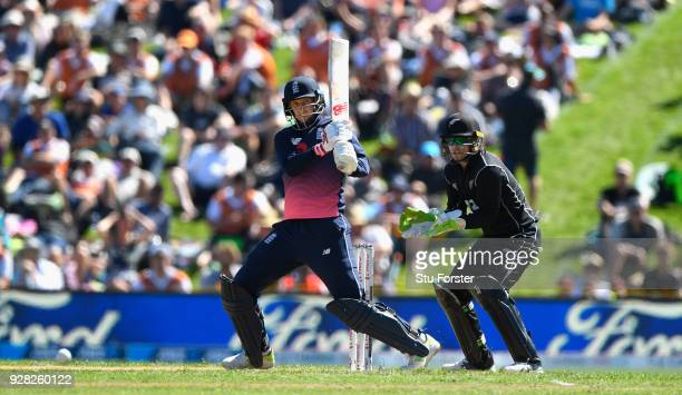 England batsman Joe Root hits out watched by Tom Latham during the 4th ODI between New Zealand and England at University of Otago Oval on March 7...