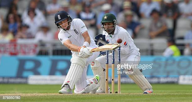 England batsman Joe Root sweeps to pick up some runs watched by Sarfraz Ahmed during day two of the 2nd Investec Test match between England and...