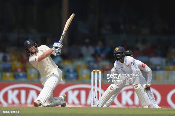 England batsman Jonny Bairstow sweeps the ball for six penneth watched by Niroshan Dickwella during Day One of the Third Test match between Sri Lanka...
