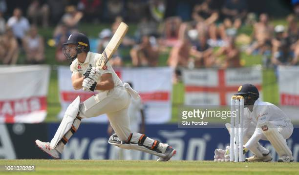 England batsman Jos Buttler prepares to reverse sweep watched by Niroshan Dickwella during Day One of the Second Test match between Sri Lanka and...