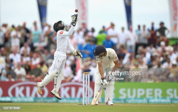England batsman Jos Buttler reacts as Sri Lanka wicketkeeper Niroshan Dickwella celebrates catching him during Day One of the First Test match...