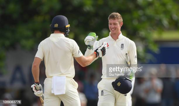 England batsman Keaton Jennings reaches his century and is congratulated by Jos Buttler during Day three of the First Test match between Sri Lanka...