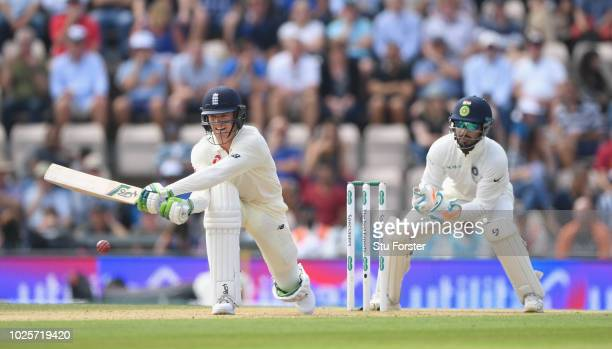 England batsman Keaton Jennings reverse sweeps a ball to the boundary watched by wicketkeeper Pant during day three of the 4th Specsavers Test...