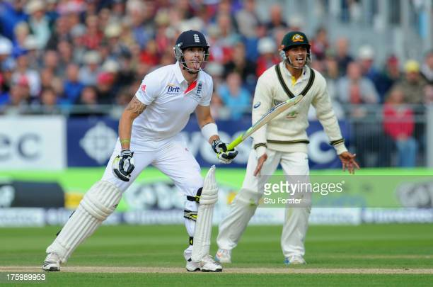 England batsman Kevin Pietersen looks on with Australia fielder Usman Khawaja as his shot is caught and he is out for 44 runs during day three of 4th...
