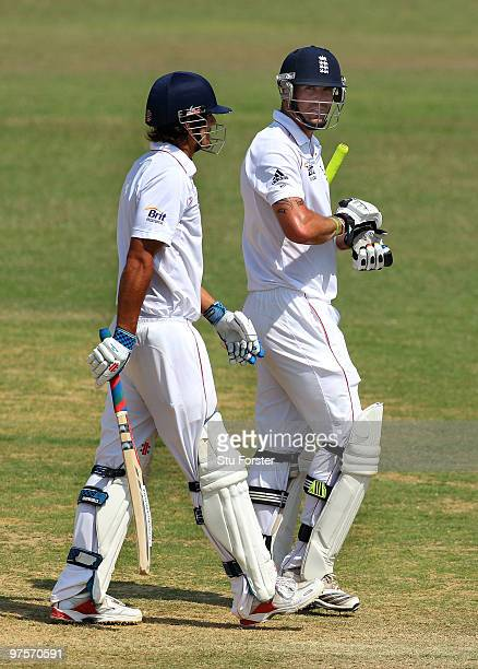 England batsman Kevin Pietersen talks to captain Alastair Cook whilst leaving the field after being bowled for 20 runs during day three of the tour...