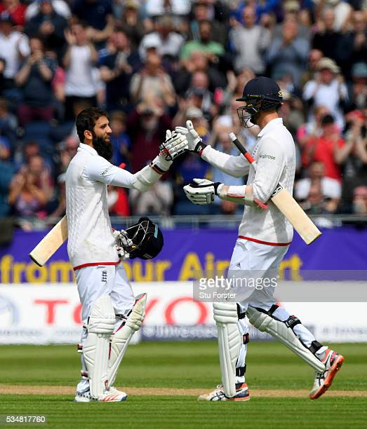 England batsman Moeen Ali celebrates his century with Steven Finn during day two of the 2nd Investec Test match between England and Sri Lanka at...