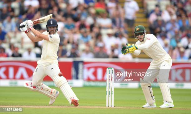 England batsman Rory Burns cuts a ball to the boundary watched by Tim Paine during day two of the First Specsavers Test Match between England and...
