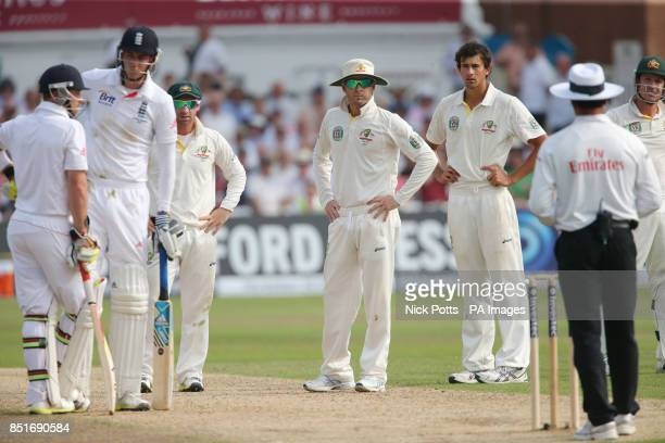 England batsman Stuart Broad stands his ground after he is caught by Australia captain Michael Clarke who looks towards Umpire Aleem Dar who gave him...