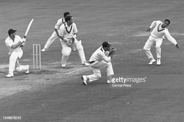 England batsman Tom Graveney plays a sweep shot to the boundary as West Indies wicketkeeper Jackie Hendriks and fielder Peter Lashley look on during...