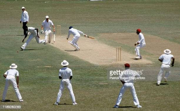 England batsman Wilf Slack is left stranded midwicket as Joel Garner of West indies fields the ball before running out Slack for 0 during the 2nd...