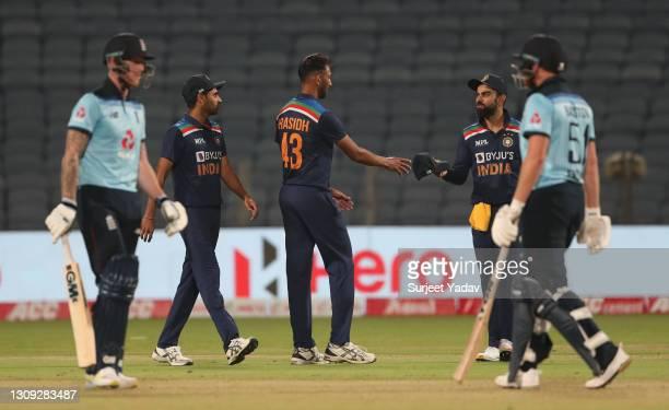 England batsmen Ben Stokes and Jonathan Bairstow look on as India captain Virat Kohli talks with bowler Prasidh Krishna during the 2nd One Day...
