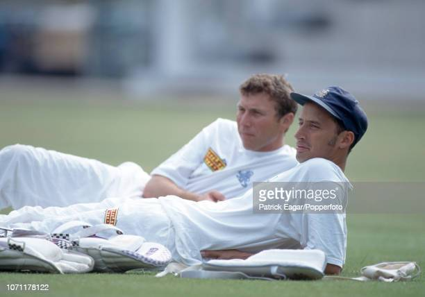 England batsmen Nasser Hussain and captain Mike Atherton relax on the grass during a nets session before the 2nd Test match between England and India...