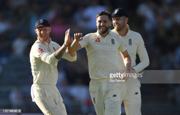 England bowler Chris Woakes celebrates With Ben Stokes and Dom Sibley after taking the wicket of Faf du Plessis after review during Day Two of the...