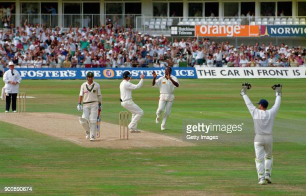 England bowler Devon Malcolm celebrates with short leg fielder John Crawley after dismssing South Africa batsman David Richardson lbw for 3 runs on...