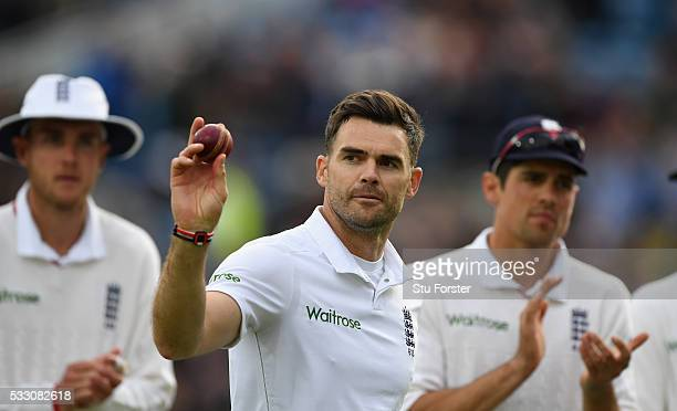 England bowler James Anderson is applauded by Stuart Broad and Alastair Cook as he shows off the ball after taking 5 wickets during day two of the...