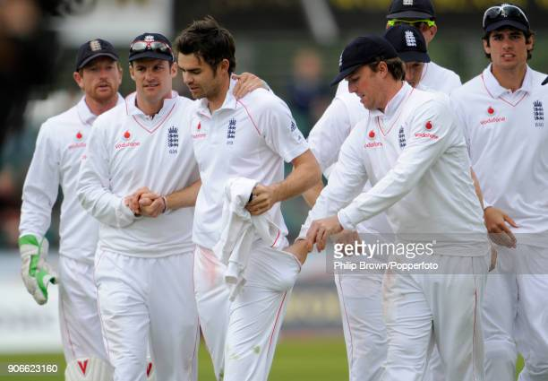 England bowler James Anderson is congratulated by captain Andrew Strauss after taking five wickets as teammate Graeme Swann takes the ball from his...