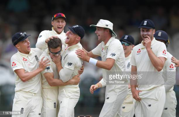 England bowler Joe Denly is congratulated by team mates left to right Sam Curran, Joe Root, Ben Stokes, and Stuart Broad and Dom Sibley after taking...