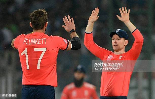 England bowler Liam Plunkettcelebrates with captain Eoin Morgan after he dismissed New Zealand batsman Colin Munro during the World T20 cricket...