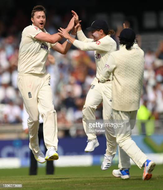 England bowler Ollie Robinson celebrates with team mates after taking the wicket of Rahane during day one of the Third Test Match between England and...