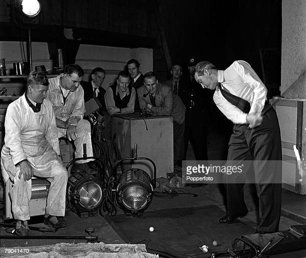 England British actor Ray Milland is pictured practising his golf swing on the set of the film White Heather watched by members of the production crew