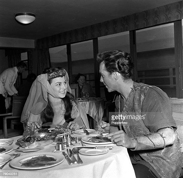 "England British actress and ex waitress Joan Rice talks with English film star Richard Todd as they eat dinner on the set of the film ""Robin Hood"""