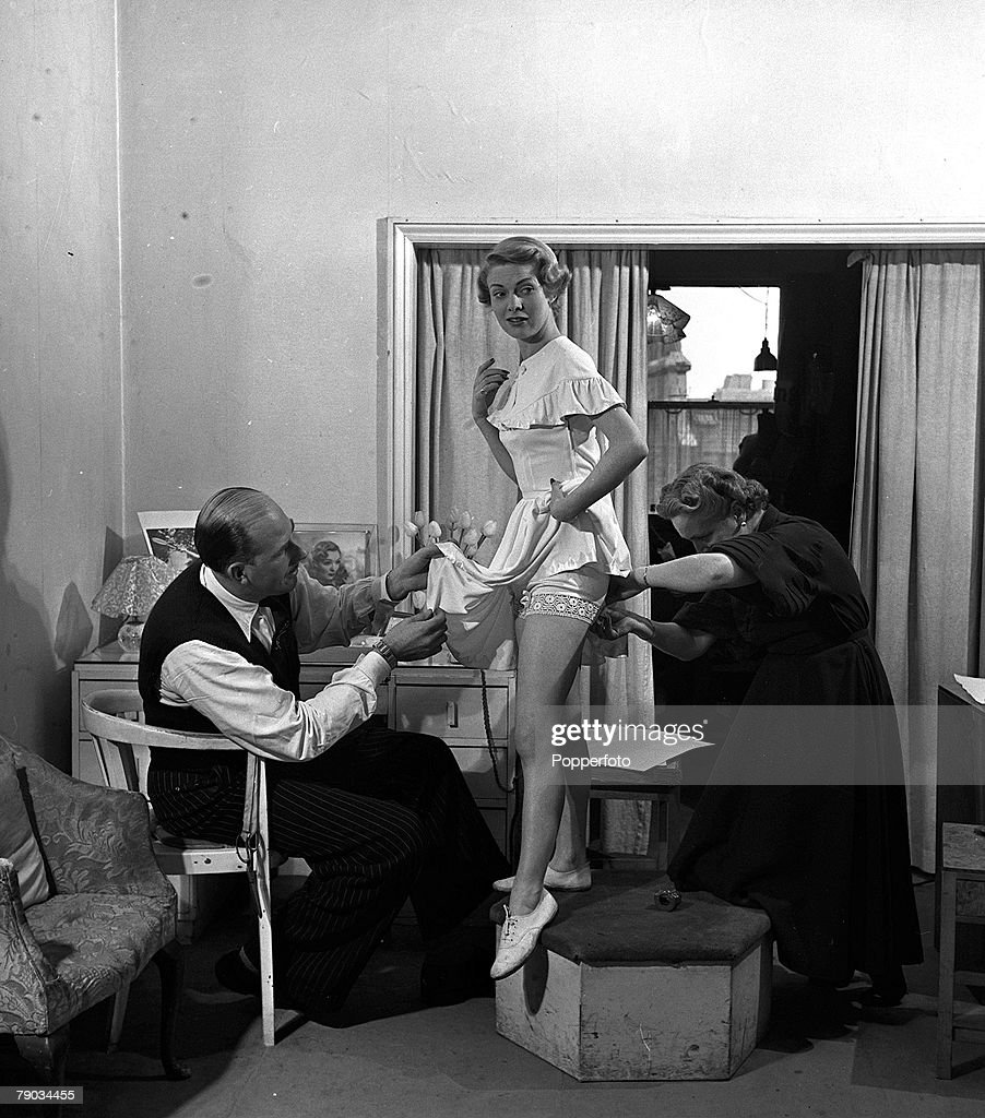 England, 1950, British fashion designer Colonel Teddy Tinling is pictured with a model wearing a tennis costume that he designed which was worn by US tennis star Gussie Moran